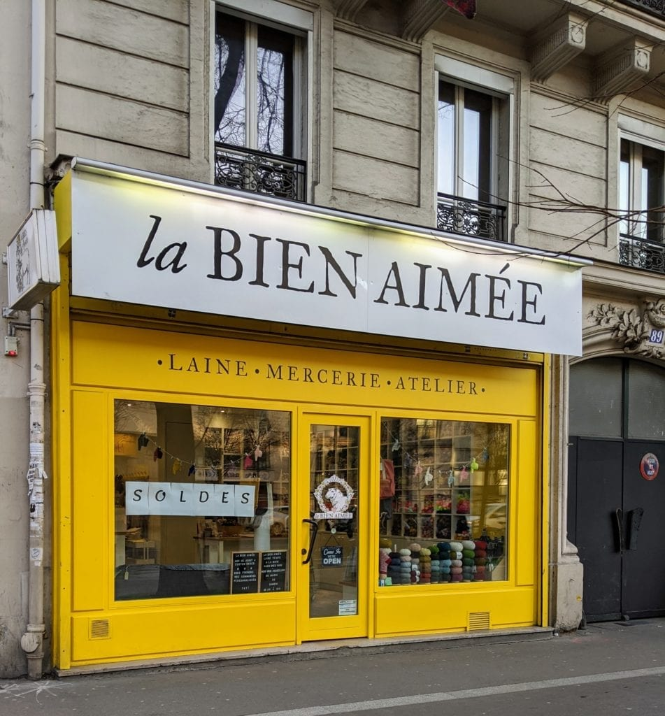 The La Bien Aimée storefront features a striking bright yellow façade beneat beige apartments.
