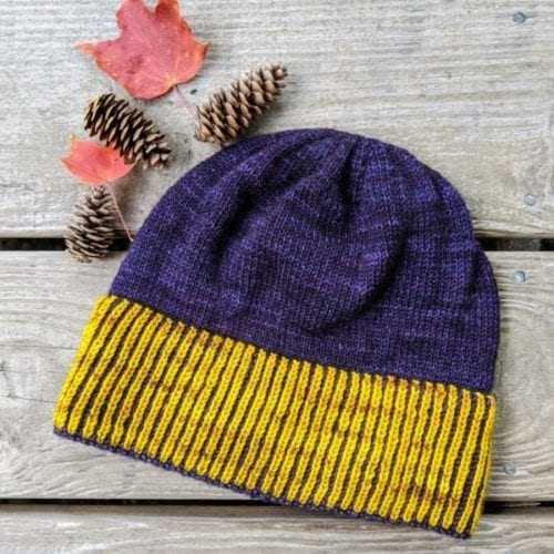 A purple beanie or toque with bright yellow vertical stripes in the brim.