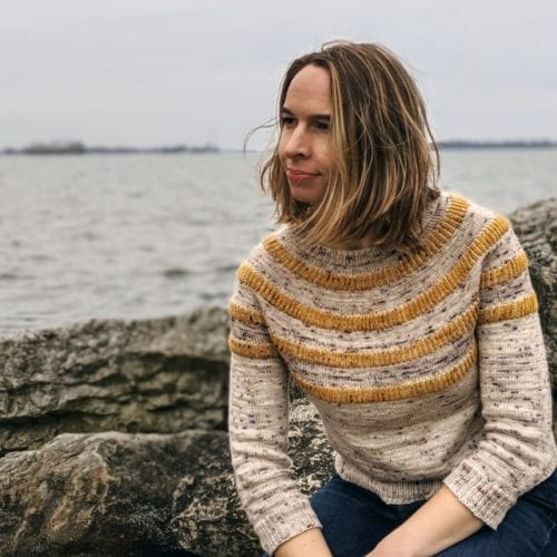 Rachel sitting on a boulder in front of Lake Erie wearing her Strikethrough sweater design.