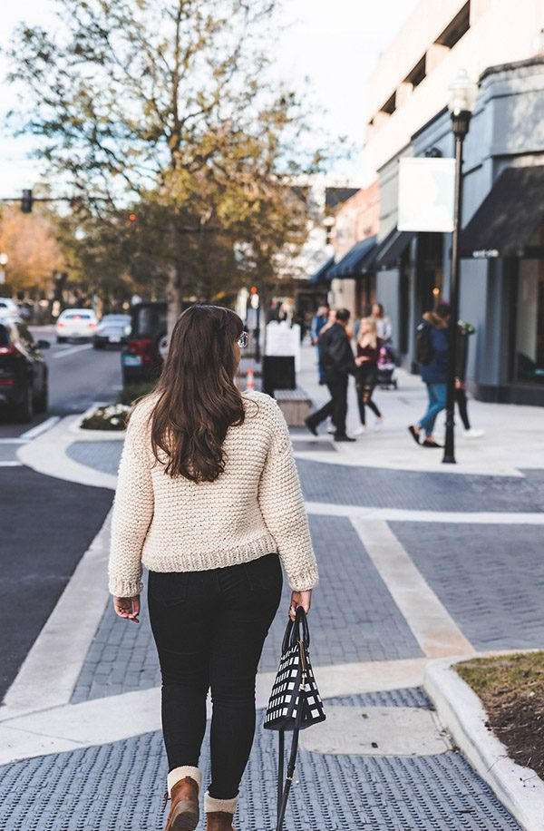 Sewrella walking away from the camera wearing her Simple Knit Sweater, a beginner knit sweater pattern.