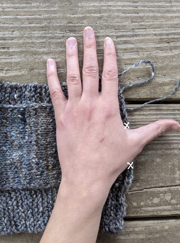 My left hand lies on top of one of my unseamed fingerless gloves, demonstrating how to mark the thumbhole.
