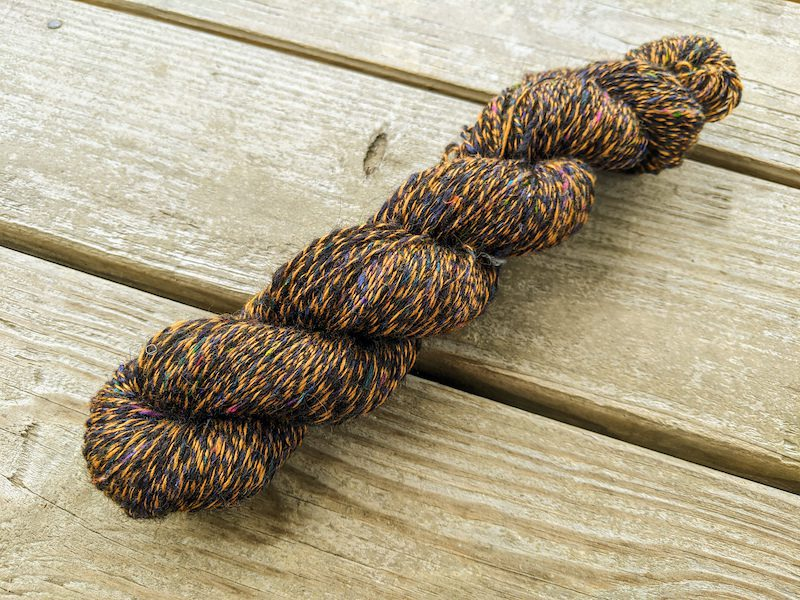 A 2-ply skein of black wool with colorful nepps plies with red eri silk.
