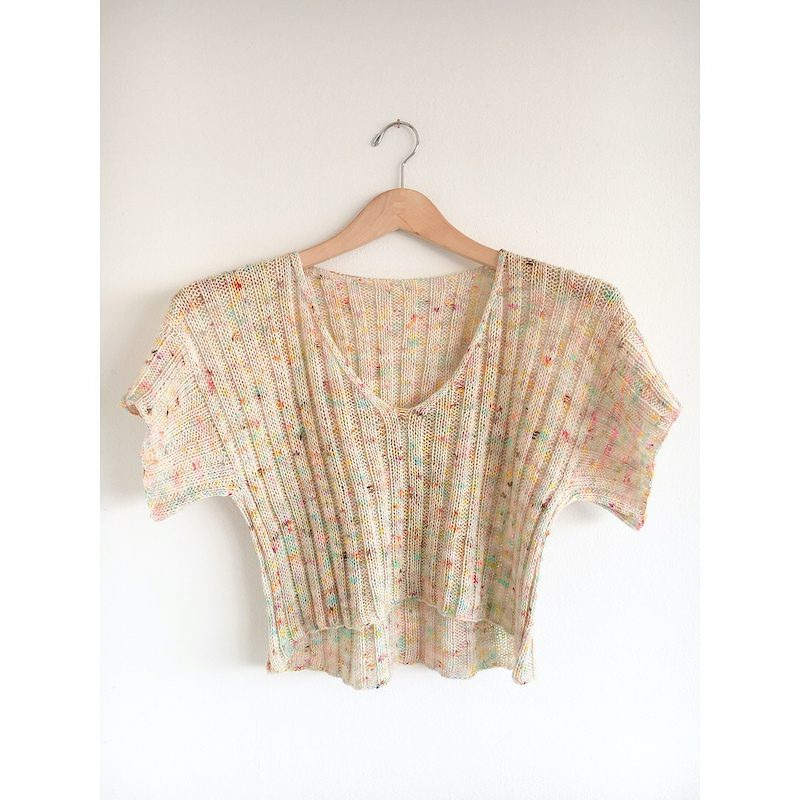 A creamy, speckled Ripple Crop Top hangs from a wooden hanger on a wall.